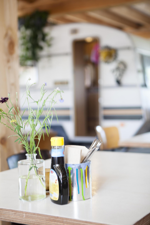 Tafel met vaasje bloemen, stroopfles en verfblik met bestek